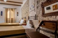 The stone wall provides texture and interest to this triple room in Creta Villa Hotels in Ierapetra south Crete